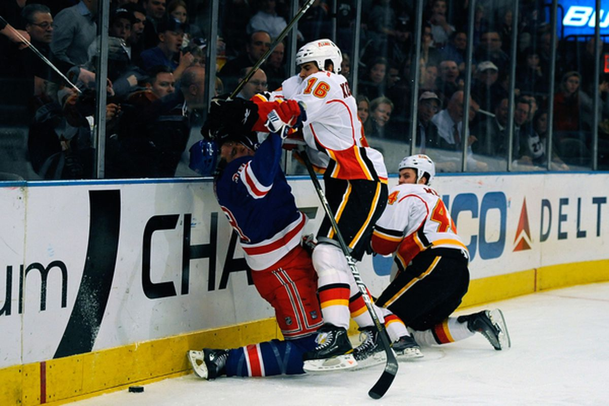 NEW YORK - NOVEMBER 22:  Tom Kostopoulos #16 of the Calgary Flames checks Michael Sauer #38 of the New York Rangers during the first period on November 22 2010 at Madison Square Garden in New York New York.  (Photo by Lou Capozzola/Getty Images)