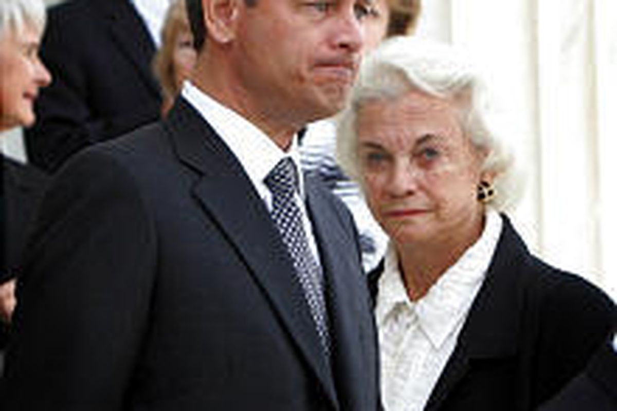 Supreme Court nominee John Roberts, a pallbearer for Chief Justice William H. Rehnquist, walks past Justice Sandra Day O'Connor as Rehnquist's casket is brought to the Supreme Court's Great Hall Tuesday.