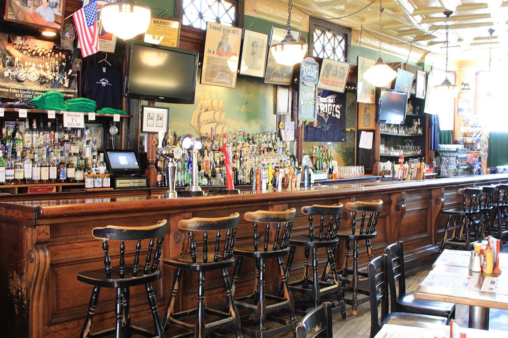 The bar at Doyle's Cafe, with high chairs lined up in front of a wooden bar, sunlight streaming in, and a television, American flag, and other decor on the green wall