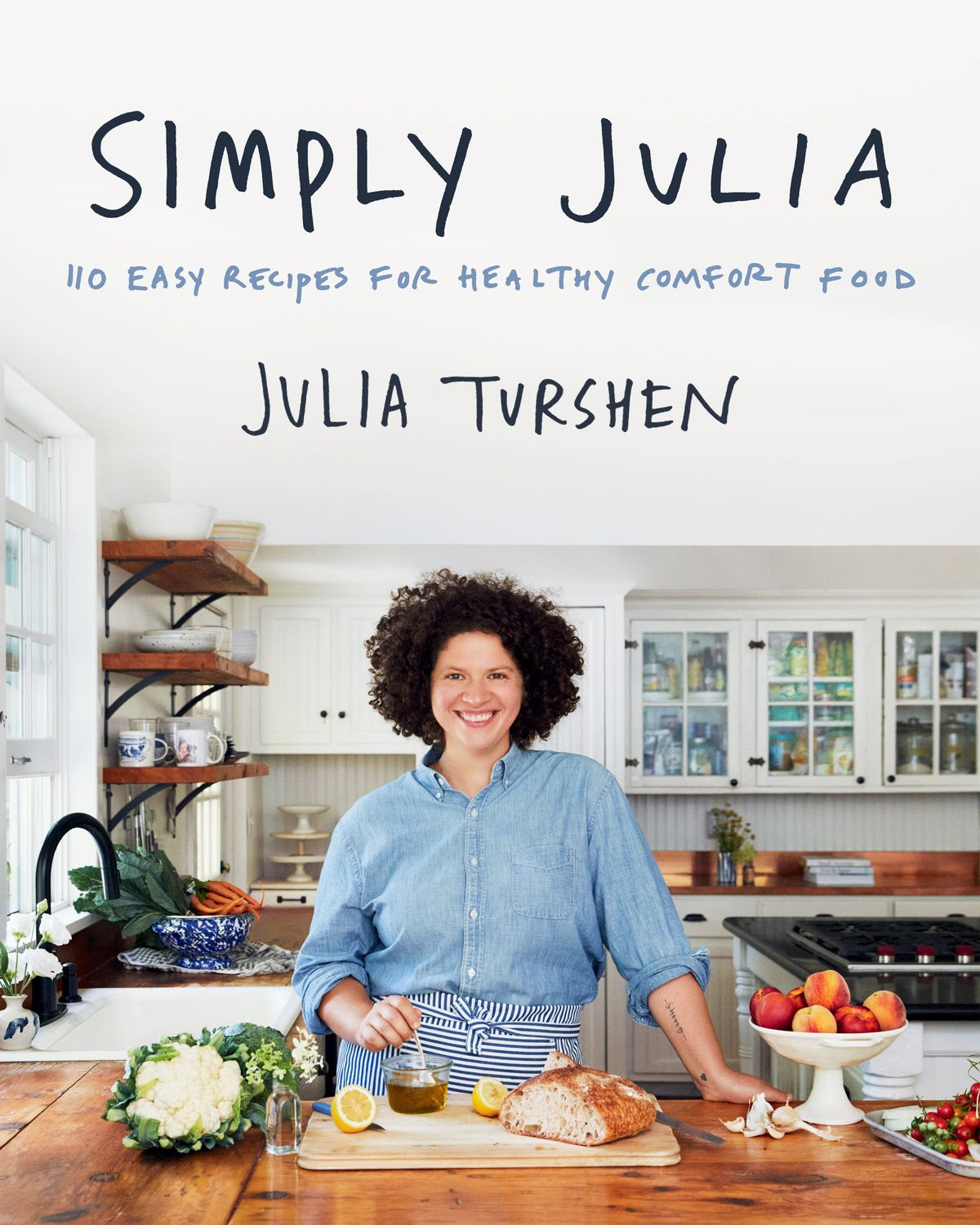A cookbook cover with a woman in a kitchen with a cutting board placed in front of her, a bowl of peaches, and a head of cauliflower