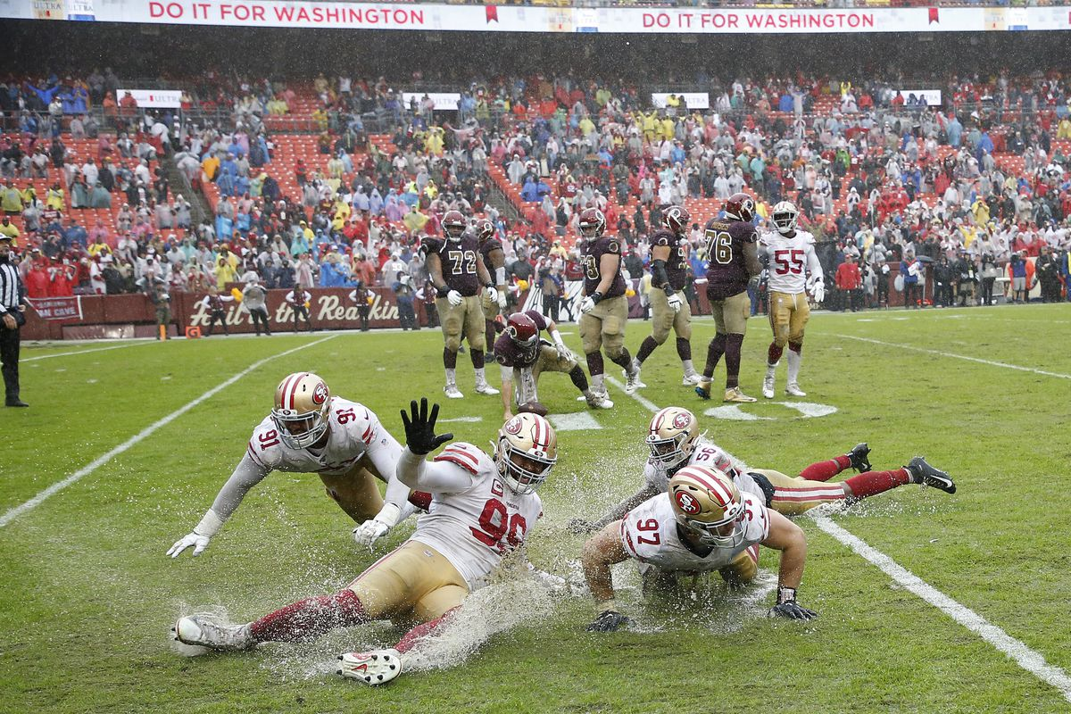San Francisco 49ers defensive end Arik Armstead, defensive tackle DeForest Buckner, defensive end Nick Bosa, and middle linebacker Kwon Alexander celebrate by sliding on the wet field after the final play against Washington at FedExField.