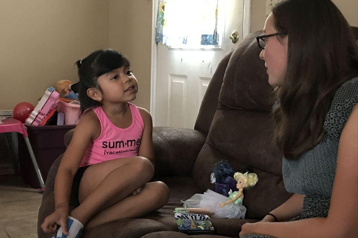 Naylin Lopez, 6, talks with her teacher, Annemarie Minor, in her home.