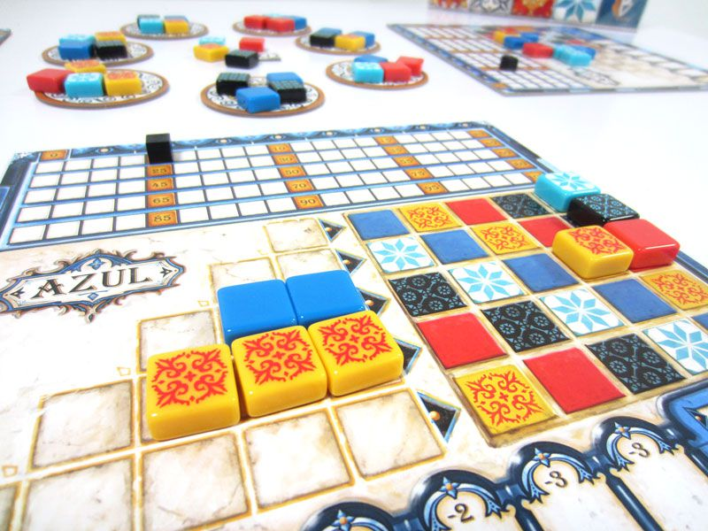A series of mosaic tiles on a board. Colors vary from blue to yellow, red, and black.