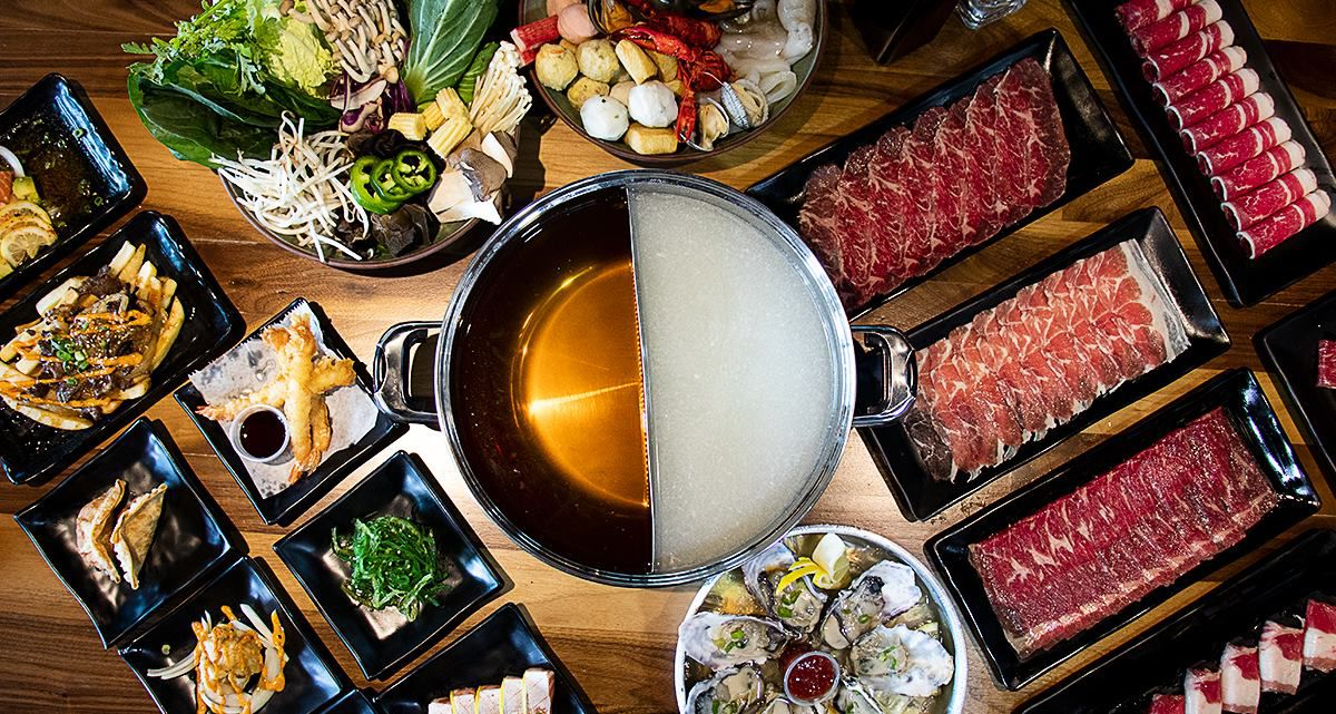 A hot pot setup with broth in the middle, meats, and sides