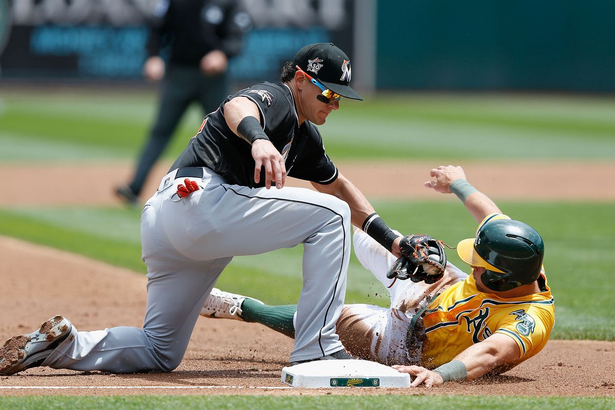 The Miami's Derek Dietrich tags out Oakland's Chad Pinder in an interleague game from this past May. (GettyImages)