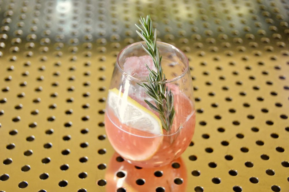 A pink cocktail in a stemless wine glass.