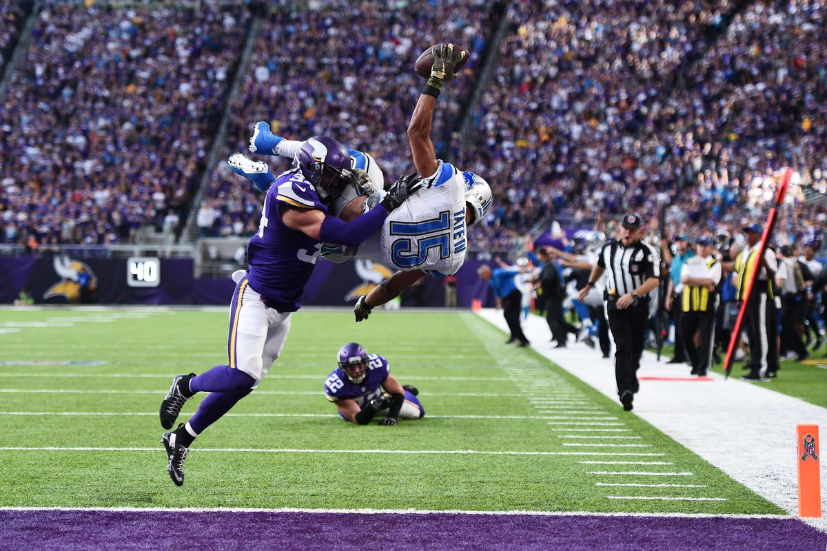 Golden Tate the Detroit Lions leaps into the end zone for the go ahead touchdown while Minnesota Viking Andrew Sendejo tries to tackle him.