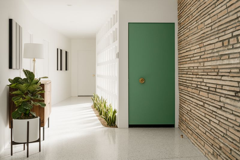 The home's entryway has a green door, plants, and a stone wall.