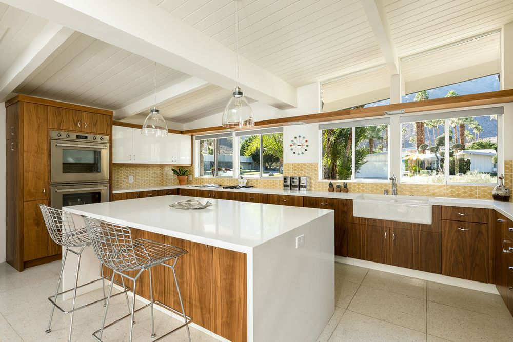 A midcentury modern kitchen with white countertops and a white wooden ceiling. The cabinetry is wooden.