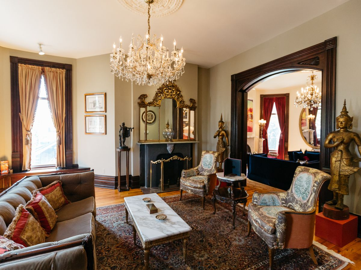 The interior of the Inn at 97 Winder in Detroit. There is a couch, arm chair, tables, chandelier, a large mirror, and floor to ceiling windows with drapes.