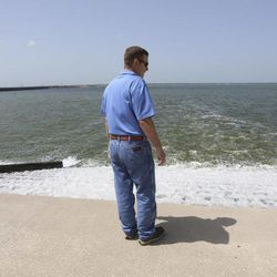 In this photo Wednesday, July 9, 2014, Chris Zachry, wetlands project manager for the Tarrant Regional Water District, watches clean water from a man made wetland project flow into the Richland Chambers Reservoir near Fairfield, Texas. As slow-moving, turbid water snakes through a man-made wetland, phosphorous and nitrates are slowly filtered out through shallow ponds full of lush vegetation and water birds until, a week later, the water runs clear as a creek  directly into a North Texas drinking supply.