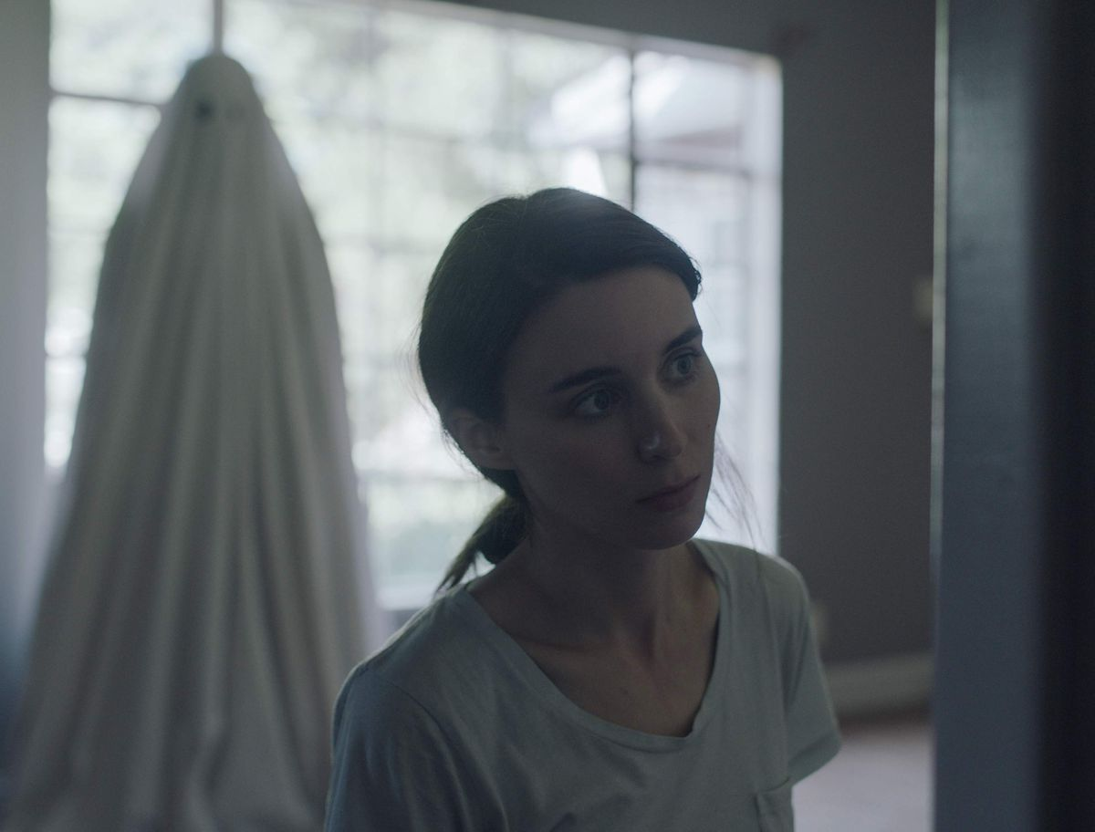 A ghost stands behind Rooney Mara