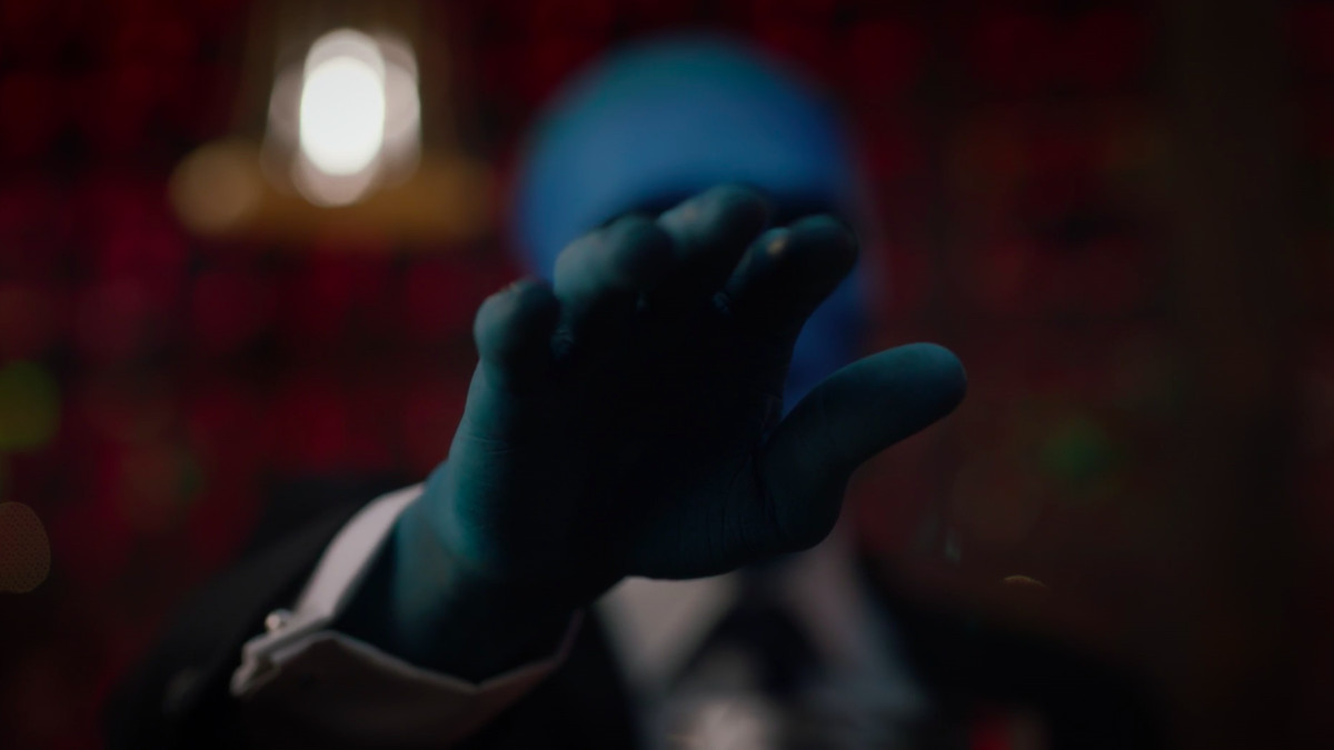 doctor manhattan raises his hand while wearing a blue mask