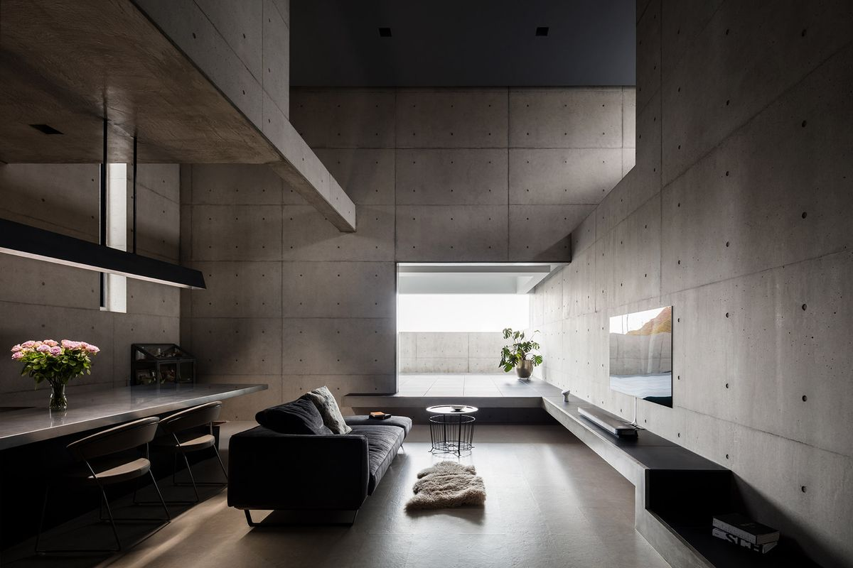 A living area with concrete walls, a couch, table, and windows.