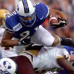 09.12.98 - BYU tight end Tevita Ofahengaue flies over ASU defenders after a catch in the first quarter during Saturday night's game at Cougar Stadium. PHOTO BY GARY MCKELLAR