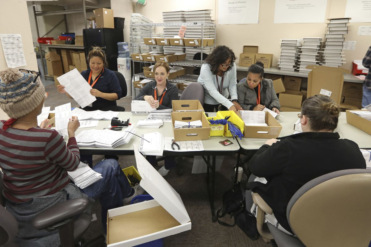 In this Wednesday, Oct. 31, 2018, photo, election workers process returned voted ballots in the Salt Lake County Government Center, in Salt Lake City.
