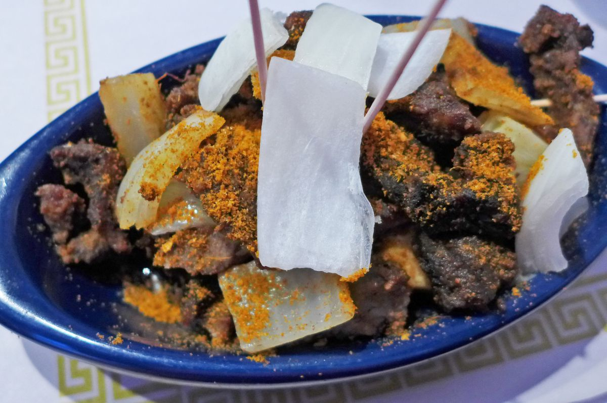 An oblong bowl of peanut dusted kebabs and onions, with wooden sticks protruding.