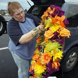Rachel Billings delivers flowers at the Life Center Church sanctuary in Tacoma, Wash., Friday, Feb. 10, 2012 in preparation for the memorial for Susan Cox Powell, Charlie Powell and Braden Powell.