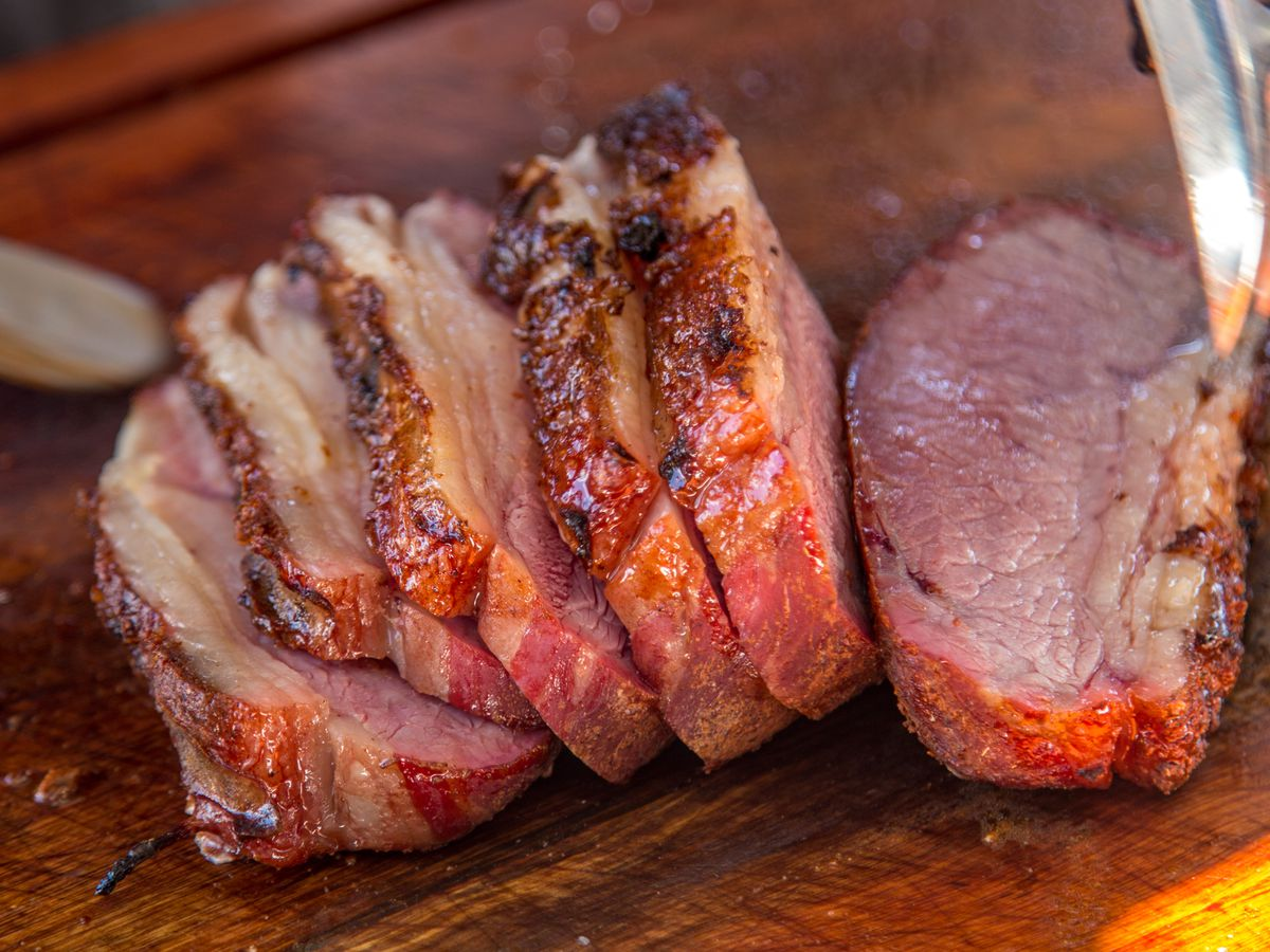 A sliced steak on top of a wooden cutting board
