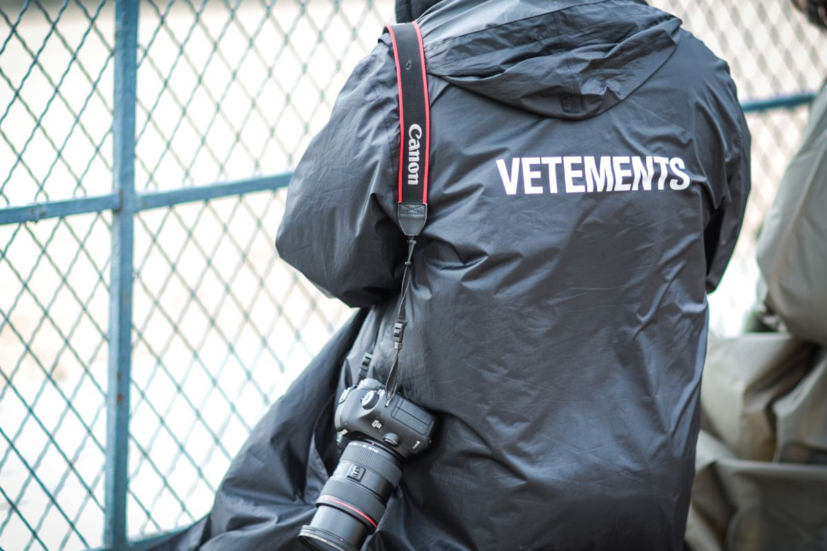 A photographer wearing a Vetements jacket during Paris fashion week fall 2016