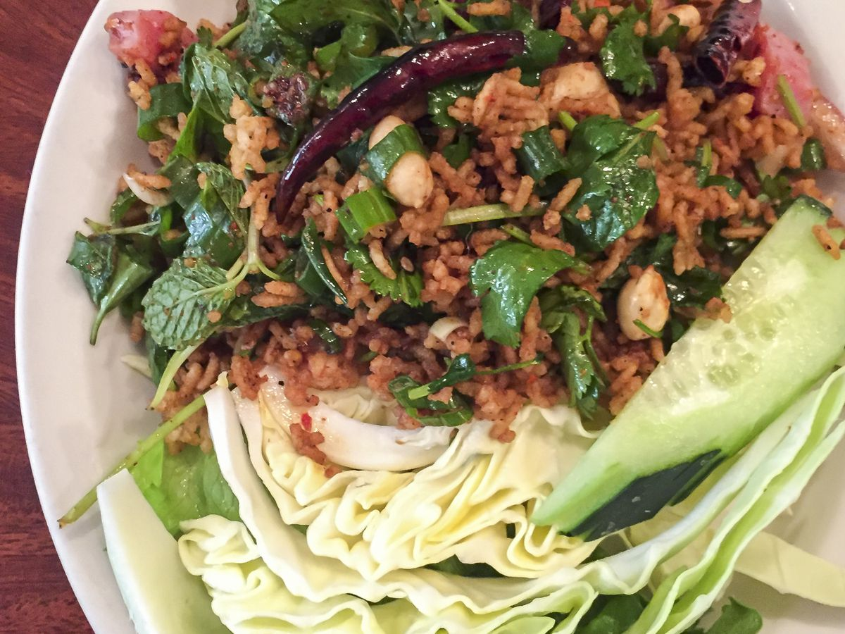 Close up image of a plate of fried rice with basil and lettuce