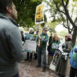 Rocky Mountain Power communications manager Spencer Hall speaks with power customers after they delivered a petition with 4,000 signatures demanding strong and clear action plans to transition away from coal at the company's headquarters in Salt Lake City on Wednesday, Oct. 9, 2019.