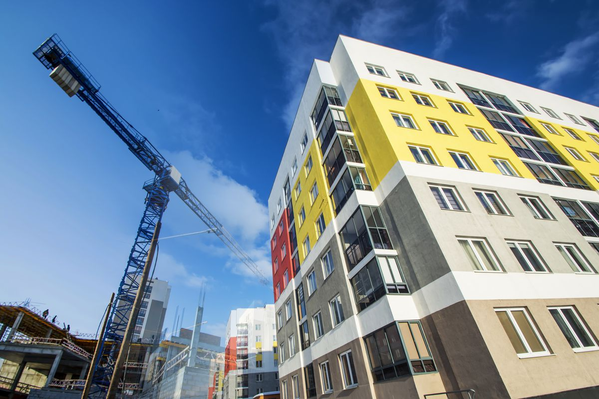 A block of modern apartment building with mutlicolored facades being built, with a crane in the background.