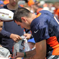 Broncos QB Chad Kelly signs autographs after practice.