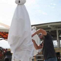 A ghost on the Wildwood N.J. boardwalk seems startled as Morey's Piers employee Jamil Dorta works on him Thursday Sept. 27, 2012. The boardwalk is adapting some of its summertime rides to a Halloween theme to try to extend the tourist season as long as possible.