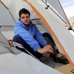 Isiah Smith puts on water shoes inside his tent as he prepares for an afternoon of paddling at Lone Rock Beach at Lake Powell on Friday, March 26, 2021. Smith, who is 17, was born completely blind with bilateral retinal detachment. He is part of the Utah Schools for the Deaf and the Blind Yacht Club, which istraining for the SEVENTY48, a 70-mile human-powered boat race from Tacoma to Port Townsend, Wash. Members of the yacht club built their boat for the race by hand.