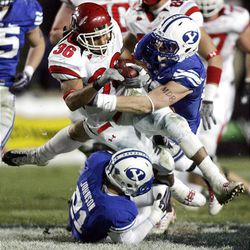 BYU's Scott Johnson (bottom) and teammate Andrew Rich combine to bring down Eddie Wide of Utah during the second half of play at LaVell Edwards Stadium in Provo Saturday. BYU won in overtime 26-23.
