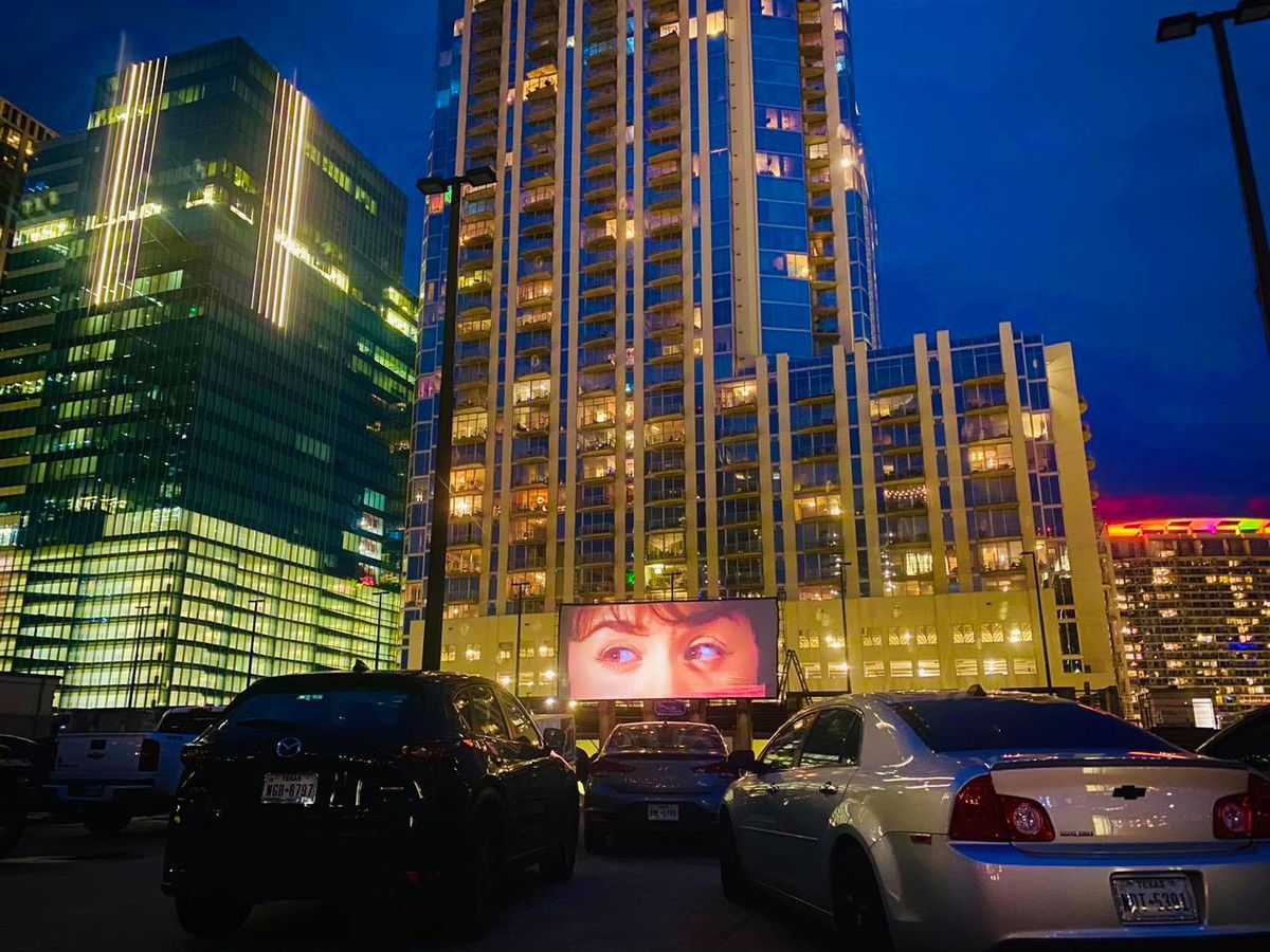 An outdoor movie screen with a close-up image of someone's eyes amid a background of tall lit-up skyscrapers and a row of cars in the foreground