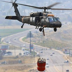 A Blackhawk helicopter flies to dip water as  a fire burns near Weber Canyon on Tuesday, Sept. 5, 2017.