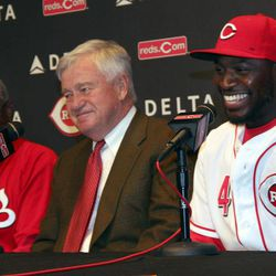 Cincinnati Reds Brandon Phillips laughs with with Reds owner Bob Castellini, center and manager Dusty Baker, left, after announcing  his signing of a six year contract at Great American Ballpark in Cincinnati Tuesday April 10, 2012. Phillips signed  a six-year, $72.5 million contract through the 2017 season.