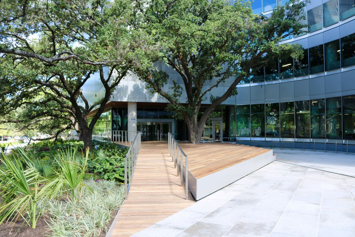 street-level plaza in front of office building windows, wooden patio and ramp, twin trees flanking entrance, landscaped garden on left