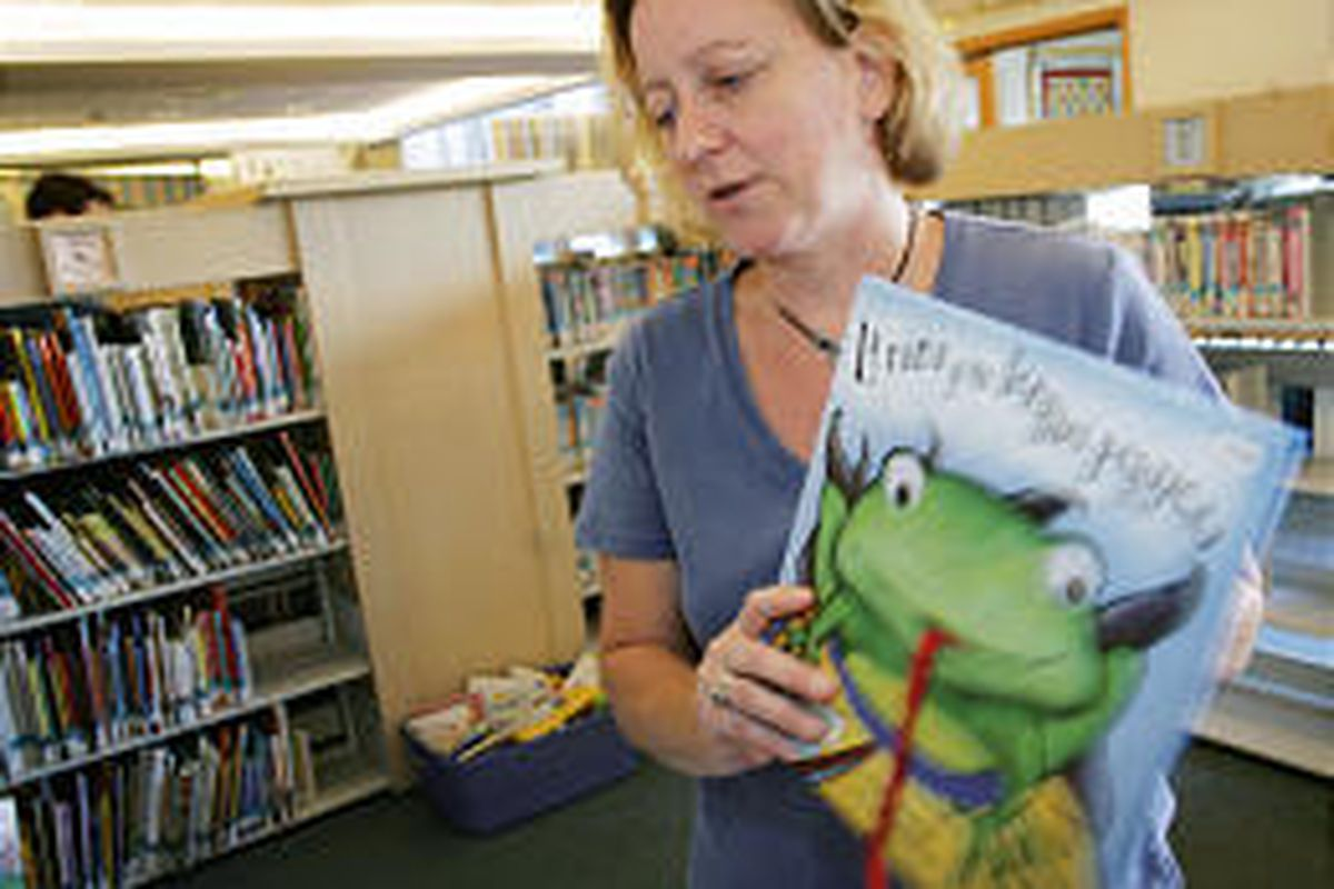Christine Johnson, children's librarian at the Denver Public Library, places one of the Spanish-language books on a shelf in the downtown branch.
