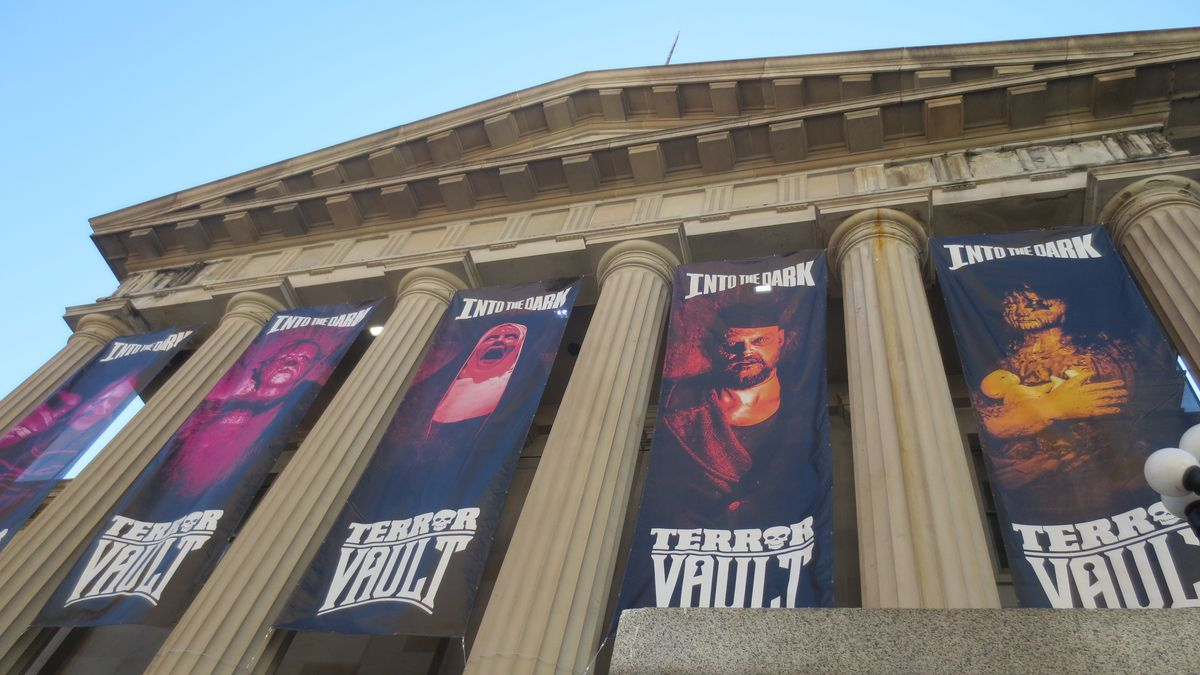 """A very low angle photo of a neoclassical building with columns and a steepled roof, with banners bearing the words """"Terror Vault"""" and horrifying faces hanging from the front."""