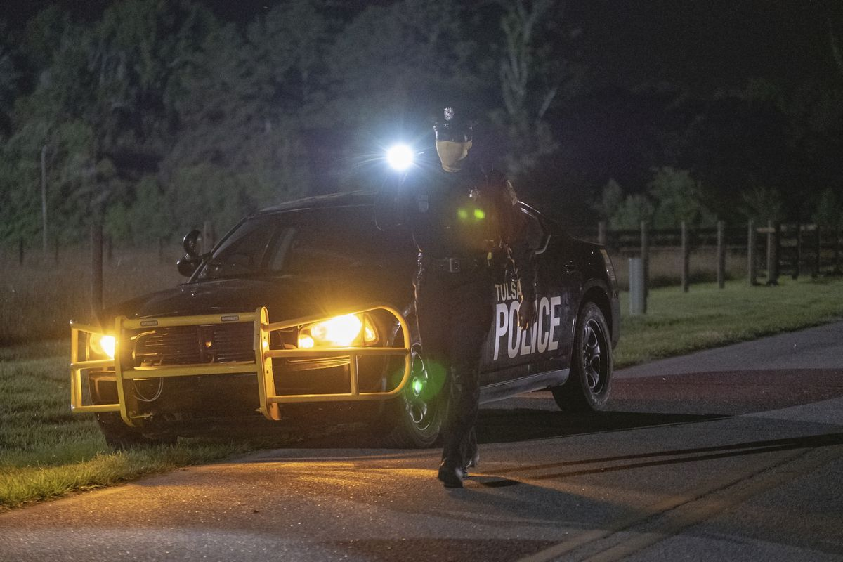 a masked police officer walks from his parked car with flashlight in hand