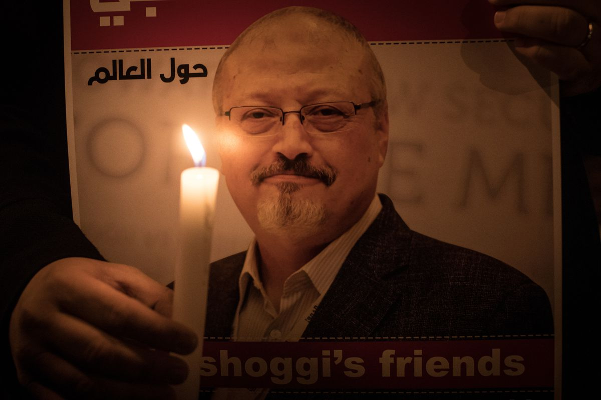 A hand holds a candle in front of a picture of slain journalist Jamal Khashoggi.