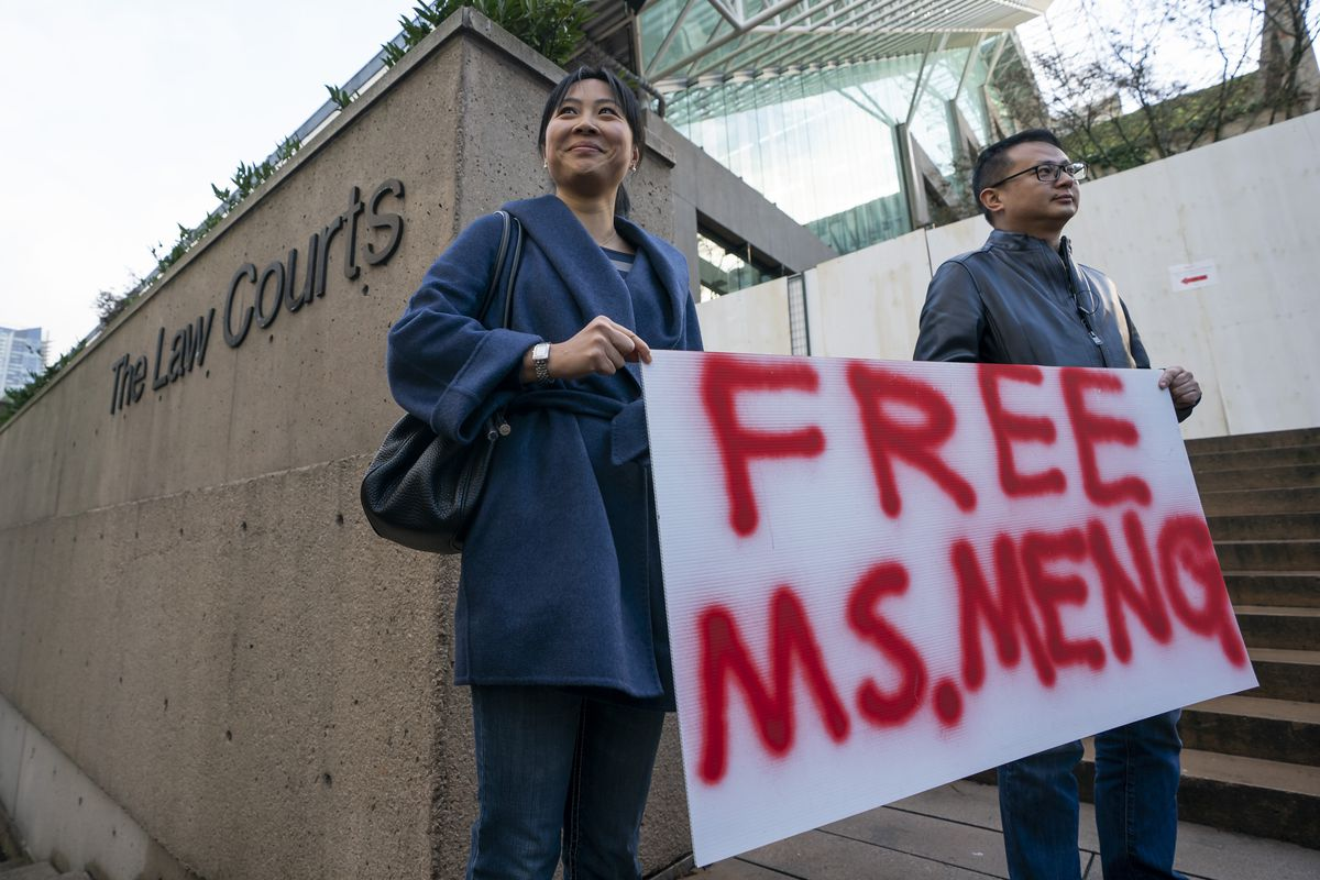 """Two people stand outside a Vancouver courthouse holding a sign reading """"Free Ms. Meng."""""""