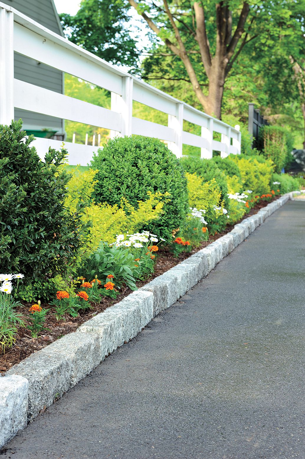 Man Adds Flowers And Plants Along Driveway Edging