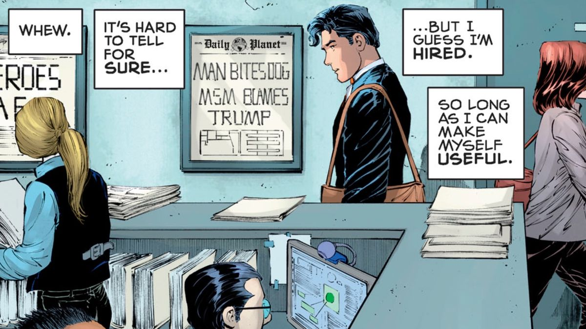 """Clark Kent walks through the bullpen of the Daily Planet. A framed front page on the wall beside him declares """"MAN BITES DOG, MSM BLAMES TRUMP,"""" in Superman: Year One #3, DC Comics (2019)."""
