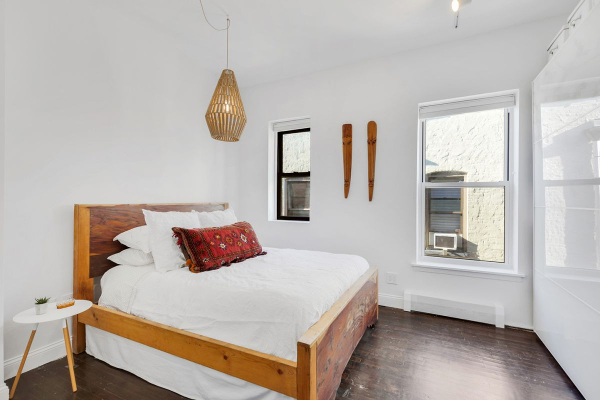 A bedroom with a large bed, hardwood floors, two windows, and white walls.