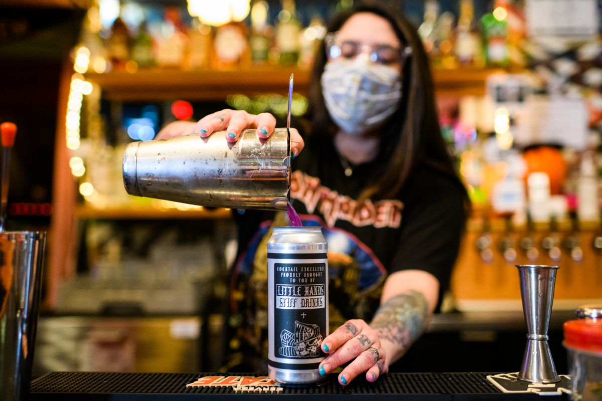 A woman pours her cocktail Sleep Witch, made with DL Franklin Vodka infused with Tea Hunter's Blue Valentine tea, into a can while wearing a mask. After starting with craft syrups and cocktail kits, Solis-Robertson launched several canned cocktails in early 2021 at NE bar WedgeHead.