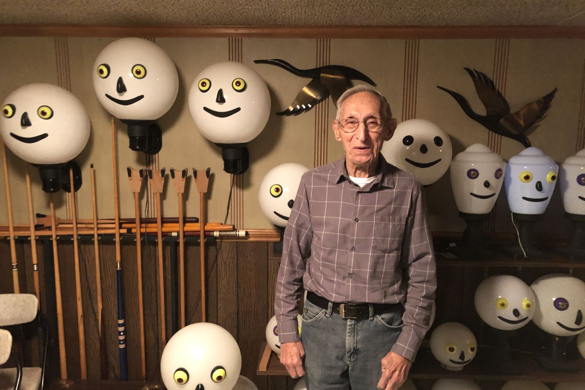 William Lange, with his lamps; when lit, they alternate colors from purple to pink to blue. He hopes to interest some manufacturer in selling them.