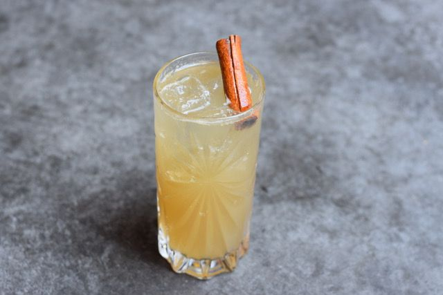 A yellow-hued cocktail in a tall glass garnished with a cinnamon stick.