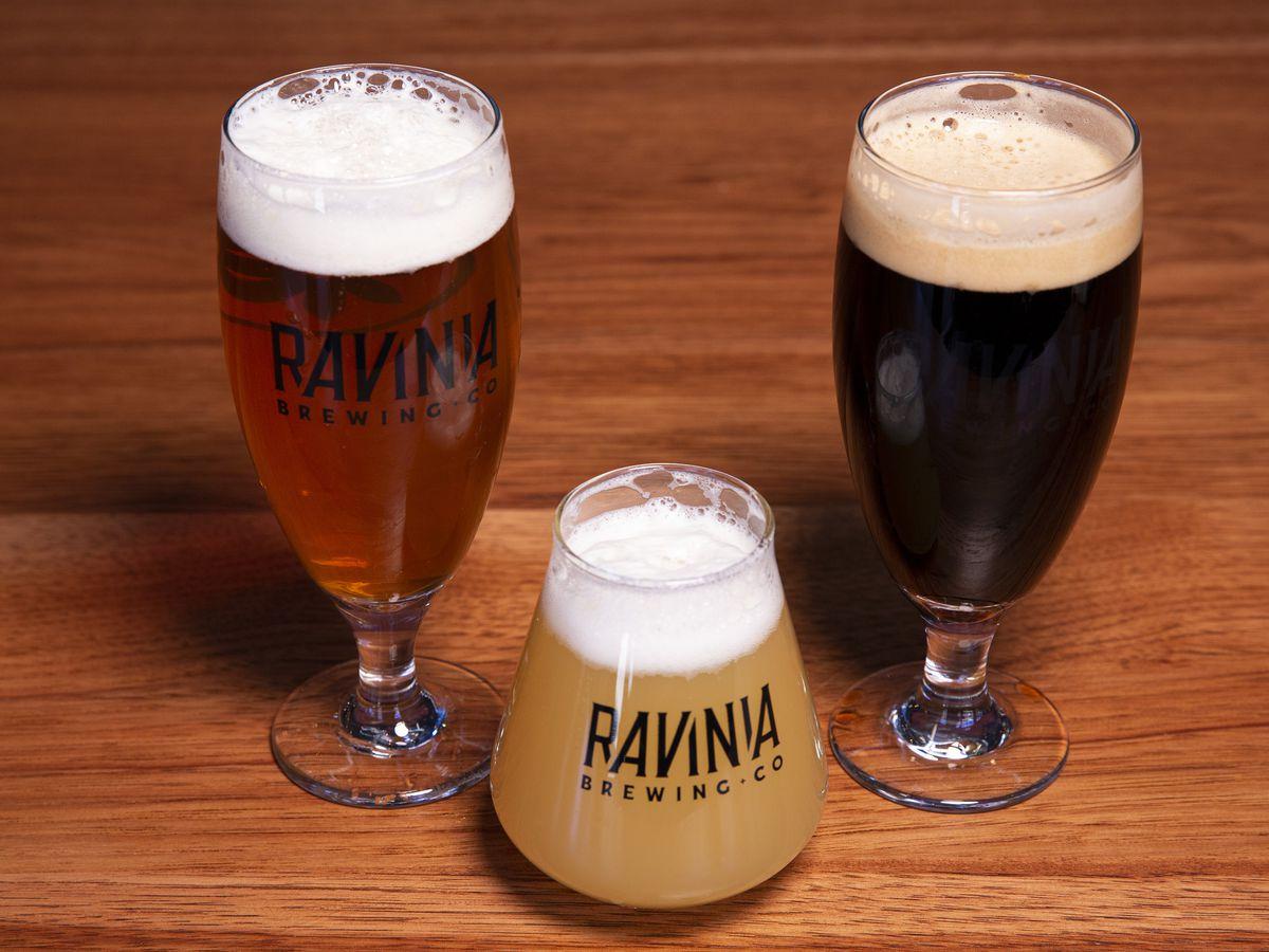 Three glasses full of beer.