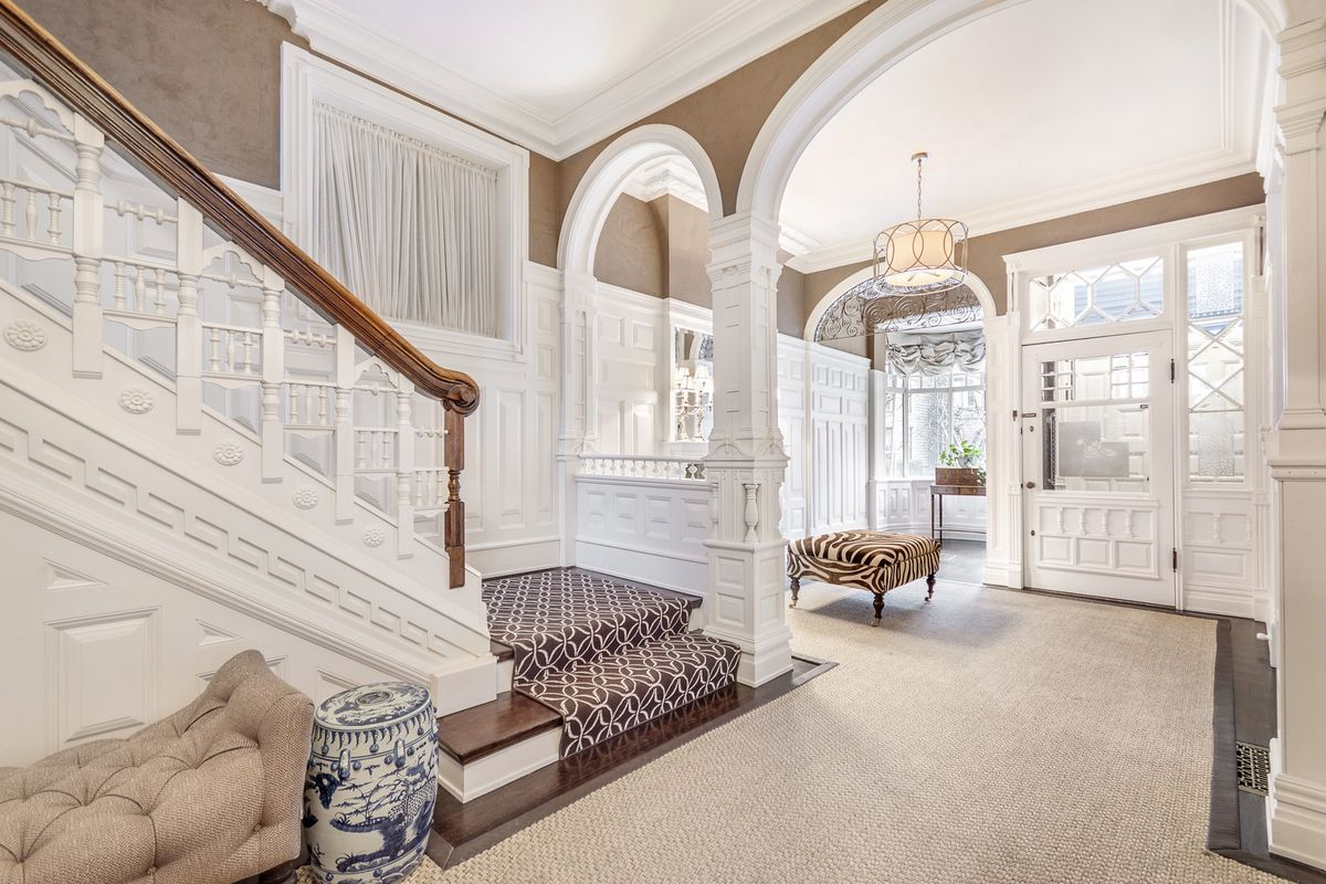 An entryway with a grand staircase and decorative archways. The walls are white and neutral.