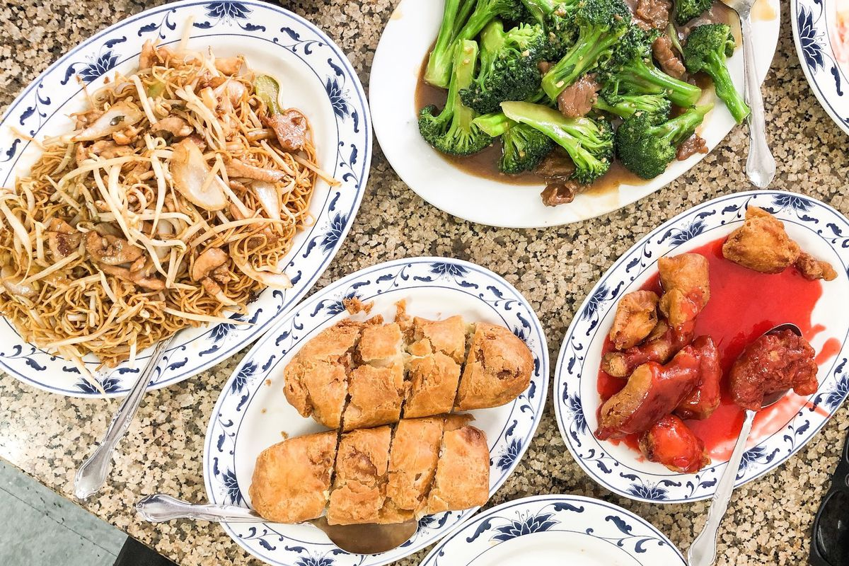 A top down look at Chinese-American food on a platter, including egg rolls.