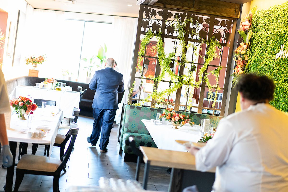A sun soaked dining room framed by greenery on the walls, white tablecloths, and a chef with his back to the camera in the foreground